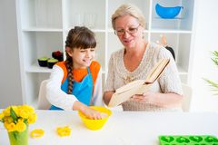 Grandmother and grandaughter. Are baking in a kitchen Royalty Free Stock Image