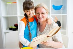 Grandmother and grandaughter. Are baking in a kitchen Royalty Free Stock Photography