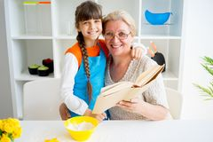 Grandmother and grandaughter. Are baking in a kitchen Royalty Free Stock Photo