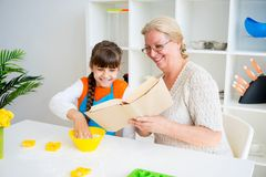 Grandmother and grandaughter. Are baking in a kitchen Royalty Free Stock Images