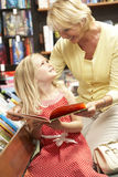 Grandmother and grandaughter in bookshop. Smiling at each other lovingly Stock Photography