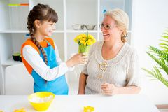 Grandmother and grandaughter. Are baking in a kitchen Stock Photo