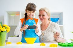 Grandmother and grandaughter. Are baking in a kitchen Stock Photos