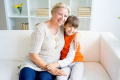 Grandmother and grandaughter. Are hugging on sofa Royalty Free Stock Image