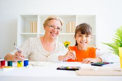 Grandmother and grandaughter. Are painting together at home Stock Images