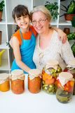 Grandmother and grandaughter. Pickle vegetables cucumbers tomatoes Stock Images