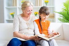 Grandmother and grandaughter. Are reading a book Stock Photo