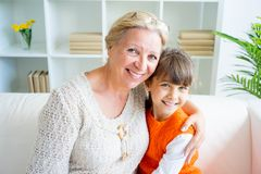 Grandmother and grandaughter. Are hugging on sofa Royalty Free Stock Photography