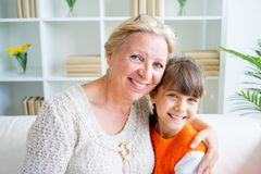 Grandmother and grandaughter. Are hugging on sofa Stock Photo