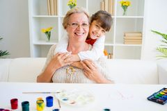 Grandmother and grandaughter. Are painting together at home Royalty Free Stock Image