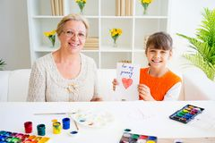 Grandmother and grandaughter. Are painting together at home Stock Photos