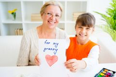 Grandmother and grandaughter. Are painting together at home Royalty Free Stock Images