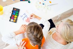 Grandmother and grandaughter. Are painting together at home Royalty Free Stock Photos