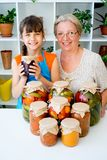 Grandmother and grandaughter. Pickle vegetables cucumbers tomatoes Royalty Free Stock Image