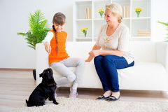 Grandmother and grandaughter. Are playing with a dog together Royalty Free Stock Photos
