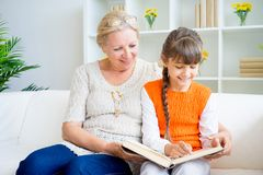 Grandmother and grandaughter. Are reading a book Stock Images
