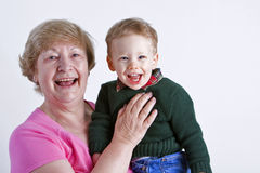 Grandmother with grandchild. Grandmother with smiling grandson on light background Royalty Free Stock Images