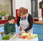 Grandmother and grandchild cooking. Grandmother and grandson cooking in the kitchen Royalty Free Stock Images