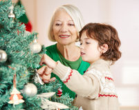 Grandmother and grandchild. Decorating christmas tree at home royalty free stock photo