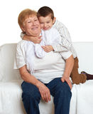 Grandmother and grandchild family portrait on white background, happy people sit on sofa. Royalty Free Stock Photo