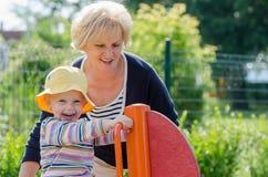 Grandmother and grandchild. Grandmother and granddaughter swinging on the playground Royalty Free Stock Photo