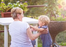 Grandmother and grandchild. Happily play in the garden. Natural light stock photography