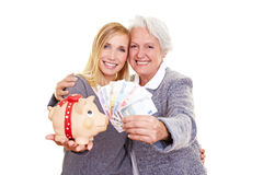 Grandmother and grandchild holding. Young and old woman holding Euro money and a piggy bank Royalty Free Stock Photography