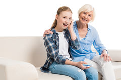 Grandmother and grandchild listening music and sitting on sofa Stock Photography