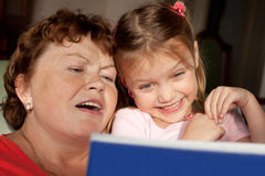Grandmother and grandchild reading. Close up of little girl reading a book with her grandmother Royalty Free Stock Photo