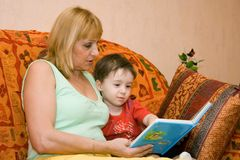 Grandmother and grandchild reading book. In the room Royalty Free Stock Photo