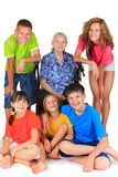 Grandmother with grandchildren. Happy grandmother surrounded by five young grandchildren, white background Stock Photo