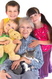 Grandmother and grandchildren. A grandmother poses happily together wit her three grandchildren while holding their cat in her lap Royalty Free Stock Image