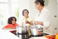 Grandmother And Grandchildren Cooking Meal At Home. Looking At Each Other Smiling royalty free stock image