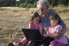 Grandmother and grandchildren with notebook Royalty Free Stock Photos