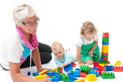 Grandmother with grandchildren playing with blocks Stock Photos