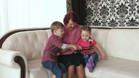 Grandmother with grandchildren playing on tablet. stock footage