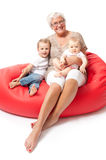 Grandmother with grandchildren on a red sofa. Grandmother on red sofa with grandchildren stock images