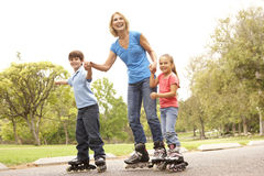 Grandmother And Grandchildren Skating In Park Stock Photo