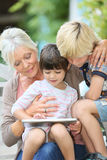 Grandmother with grandchildren on tablet Royalty Free Stock Photo
