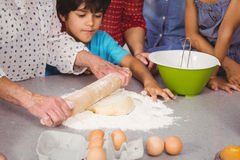 Grandmother with grandchildren using rolling pin Royalty Free Stock Photos