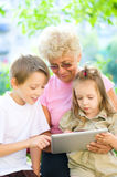 Grandmother with grandchildren using tablet. Happy grandmother with grandchildren using tablet PC, outdoors royalty free stock photo