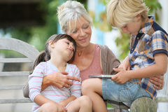 Grandmother with grandchildren using tablet outdoors stock photo