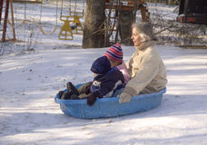 Grandmother & Grandchildren winter sliding down hill in kiddies pool. Winter sliding grandmother with grandchildren in small plastic childrens pool sliding Stock Photo