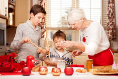 Grandmother with grandchilds in kitchen, christmas. Smiling grandmother baking cookies with young grandchilds. Christmas time. Happiness content Royalty Free Stock Photo