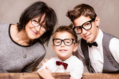 Grandmother with grandchilds posing. Beautiful grandmother posing with her grandchilds. Fashionable young boys smiling. Family portrait. Happiness Stock Photos