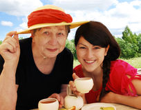 Grandmother and granddaughter. Happy grandmother and granddaughter drink tea Stock Photography