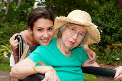 Grandmother and Granddaughter. Granddaughter with handicapped grandmother in a wheelchair in an outdoor garden setting Stock Image