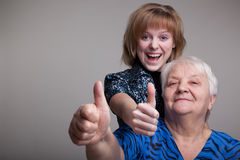 Grandmother and granddaughter. On a gray background Royalty Free Stock Photos