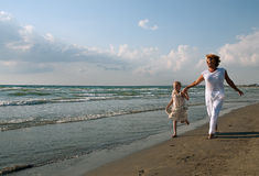 Grandmother and granddaughter. Running on a beach Stock Photo