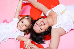 Grandmother and granddaughter. Lying on pink background Stock Photos